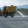 A Water Cart Spraying Heavy Water Dynamic onto Unsealed Ground